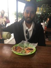Vivek eating Goose Poop Tacos
